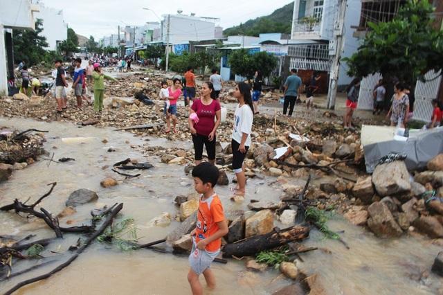 Đất đá theo dòng nước từ đoạn kênh bị vỡ chảy tràn ra khu tái định cư, ngổn ngang trên các tuyến đường ở gần đó, người dân hỗn loạn