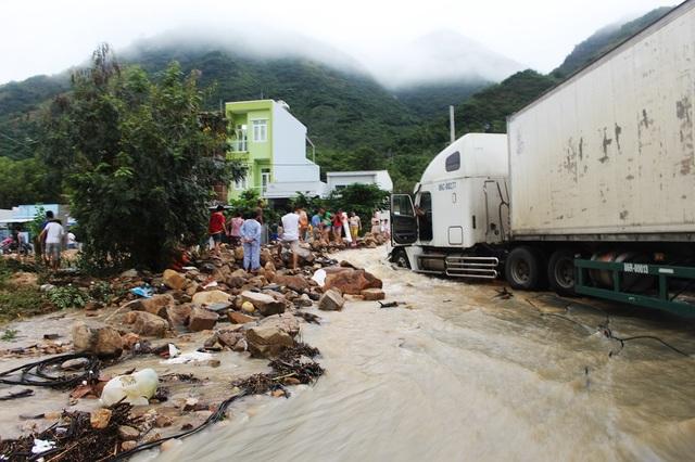 Một xe container bị mắc kẹt giữa dòng nước và đất đá sau khi kênh thoát lũ Đường Đệ (TP Nha Trang) bị vỡ do mưa lớn