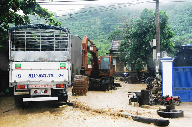 Nhiều nhà dân ven quốc lộ 1 đoạn qua TP Nha Trang bị nước lũ từ trên núi tràn xuống, cuốn trôi nhiều đồ đạc, tài sản