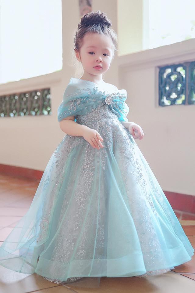 Trong bộ ảnh mới chia sẻ, Cadie hóa thành một nàng công chúa Lọ Lem với chiếc váy xanh trong suốt đính ánh kim lấp lánh. Thiết kế nổi bật với viên đá đính ở trung tâm của phần vai trễ cách điệu như một chiếc nơ. Bộ váy phảng phất phong cách các mẫu váy mà Elly Trần thường mặc trong các sự kiện trước đây.