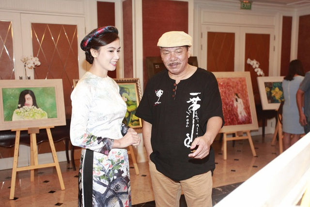 Nhạc sĩ Trần Tiến chia sẻ cảm xúc khi ngắm các bức tranh. Phía sau là hai bức vẽ lấy cảm hứng từ tình yêu áo dài của Lương Giang.