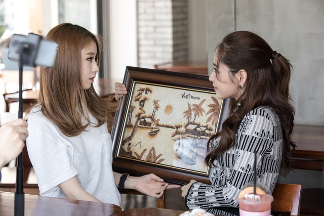 Chi Pu mang tặng Ji-yeon một bức tranh handmade phong cảnh đồng quê Việt Nam làm từ gạo cùng bộ postcard những thắng cảnh Hà Nội.