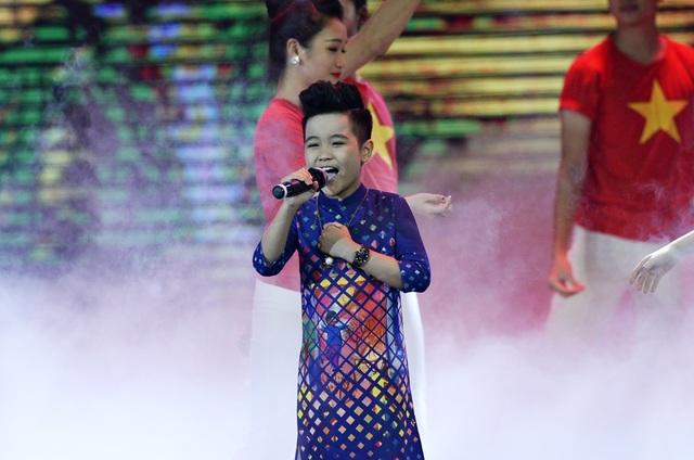 Bé Nhật Minh lại chọn một chiếc áo dài với sắc xanh, đỏ vàng đan xen để phù hợp với không khí tươi vui và tinh thần của ca khúc.