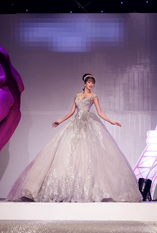 """Chiếc váy """"khủng"""" này sở hữu độ rộng của tùng váy tạo nên sự lộng lẫy. Phom dáng bồng xòe và chất liệu lấp lánh, phản quang khiến Khánh My tựa như một nàng công chúa. Bộ váy điểm xuyết bằng dải chi tiết hoa tông bạc trên thân áo."""