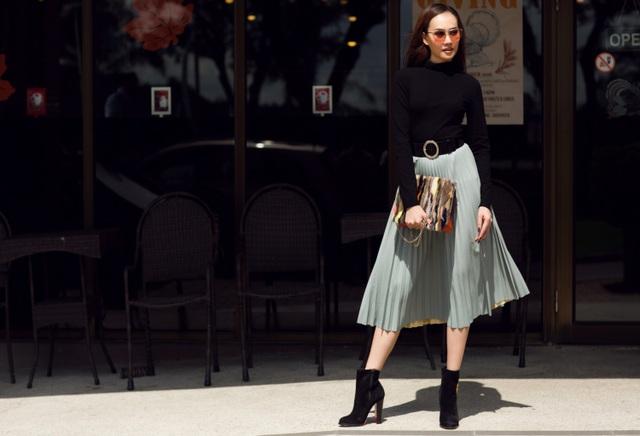 Kim Duyên kết hợp chiếc váy xếp ly xanh ghi mix-match cùng áo len đen cổ lọ.