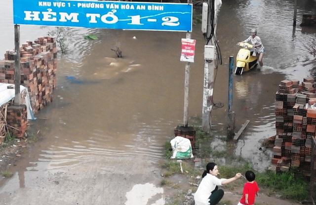 Khoảng 17 giờ, nước bắt đầu bò lên các tuyến đường ven sông