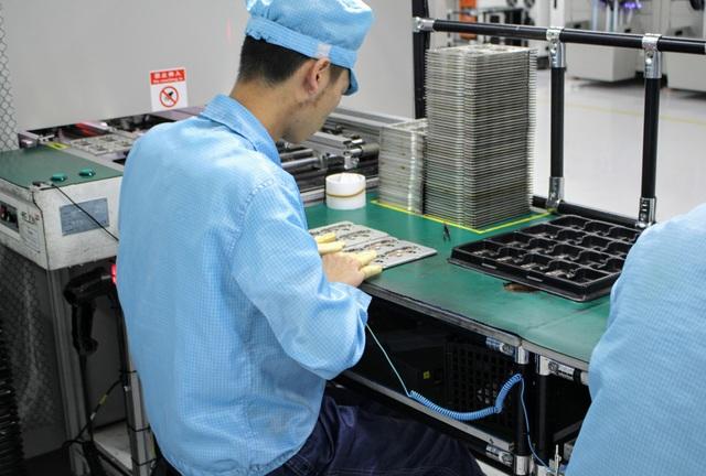 Một công nhân đang tiến hành lắp ráp chi tiết nhỏ vào smartphone