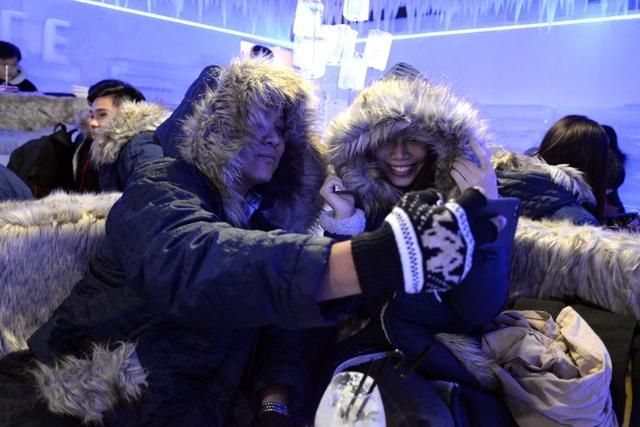 Hai bạn trẻ thích thú chụp ảnh kỷ niệm khi được mang áo khoác giữa trời nóng nực Sài Gòn.