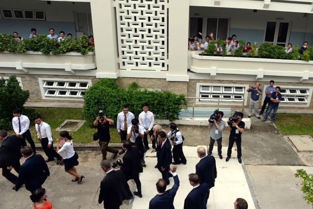Hình ảnh bác sĩ, bệnh nhân đứng dọc lan can bệnh viện vẫy chào ông François Hollande.
