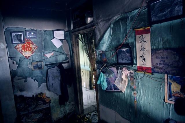 Một căn phòng bên trong chung cư còn sót lại khá nhiều đồ đạc như câu đối, những bộ quần áo hay các bức tranh treo trên tường.