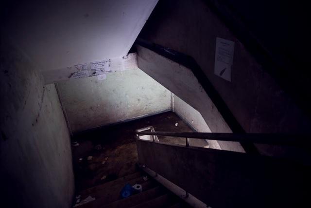 Lối đi lên cầu thang trong chung cư tối đen, rác thải nằm chất đống khắp nơi.