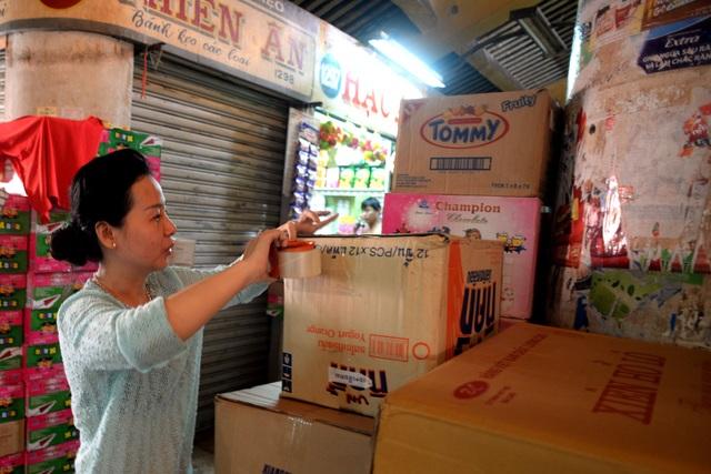 Sắp tới, các tiểu thương sẽ phải di dời qua chợ tạm ở bên cạnh để chính quyền cho trùng tu lại ngôi chợ cổ. Trong ảnh: Chị Thủy đang đóng gói hàng hóa để chuẩn bị dời đi.
