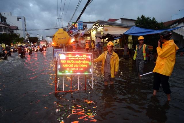 Đường Huỳnh Tấn Phát, quận 7 là một trong những điểm chịu ngập nặng nhất trong đợt triều cường lần này. Những công nhân thoát nước phải túc trực từ chiều để bơm nước và hướng dẫn người đi đường tránh những chỗ ngập nặng.