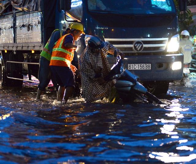 Một người đi xe máy va chạm với xe tải bị té xuống dòng nước ngập.