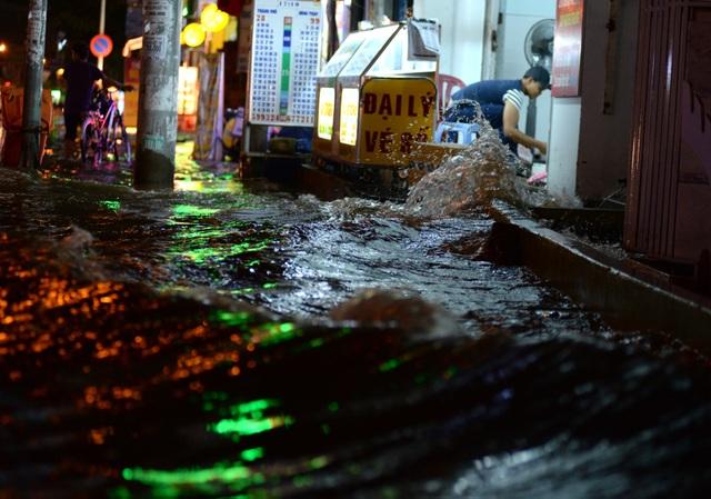 Nước lớn, tạo thành từng đợt sóng đánh thẳng vào nhà dân trên đường Huỳnh Tấn Phát, quận 7.