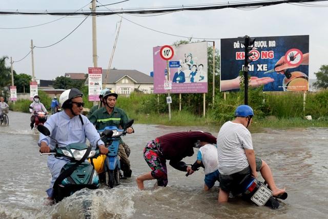 Người phụ nữ loạng choạng tay lái té cả xe xuống nước.