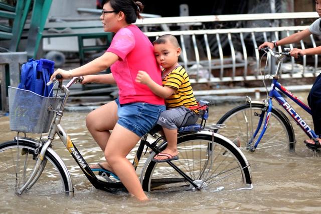 Em nhỏ nép chặt vào lưng mẹ khi đi qua đường Lê Văn Lương.