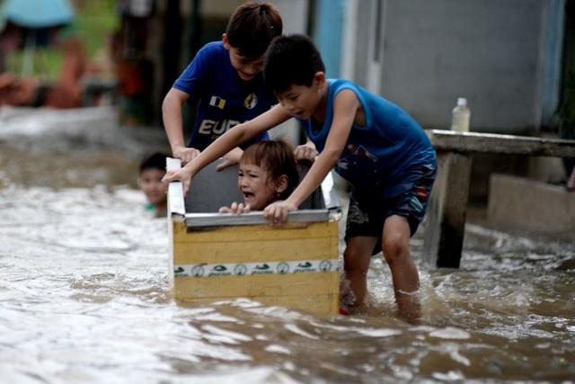 Một em nhỏ sống ở đường Lê Văn Lương sợ hãi khi nước triều dâng cao.