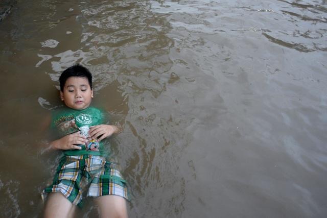 Em Tuấn thả mình trong dòng nước ngập cao 1,70m chiều 16/11.