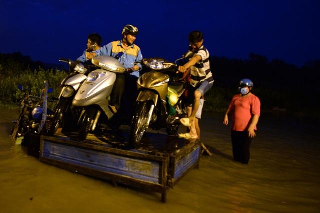 Nhiều người đi đường phải thuê xe ba gác chở qua đoạn nước ngập nặng. Mỗi chiếc xe phải trả 50 nghìn đồng tiền công.