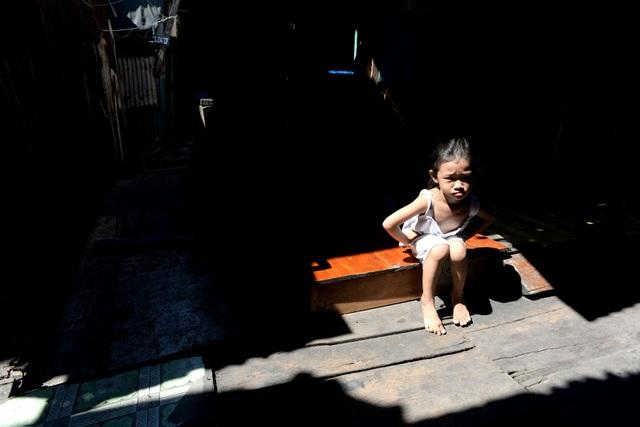 Một em bé ngồi sưởi nắng trước hiên nhà.