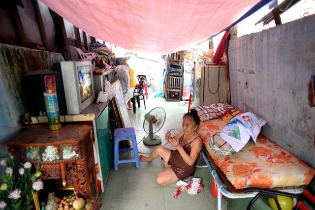 Bà Gái (63 tuổi) với ít đồ đạc bên trong căn nhà chỉ còn hai bức tường chắn, phía trên là tấm bạt che mưa nắng. Gia đình bà nằm trong diện giải tỏa, nên bà ở lại canh đồ đạc chờ các con thuê được phòng sẽ chuyển qua.