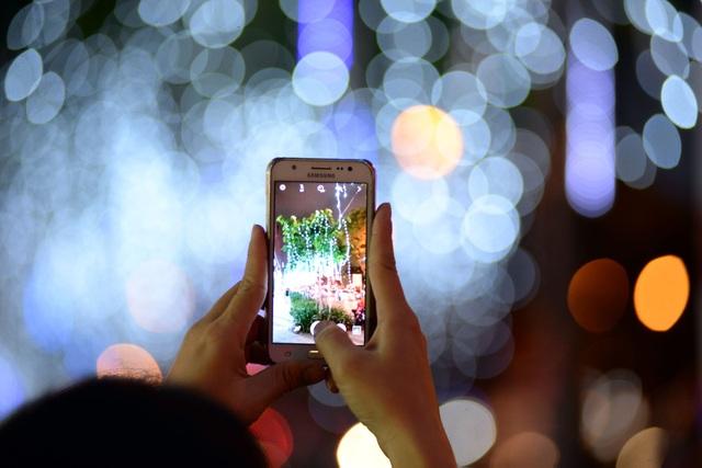 Một bạn trẻ dùng điện thoại chụp hình làm kỷ niệm.