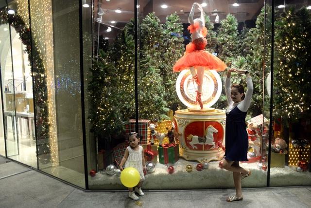 Hai mẹ con nhí nhảnh tạo dáng bên gian hàng noel ở trung tâm thương mại trên đường Hàm Nghi.