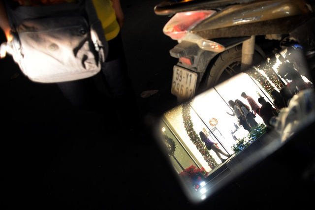 Hình ảnh không khí Giáng sinh phản chiếu qua gương xe gắn máy của người đi đường.