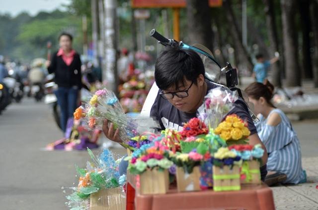 Một nam sinh viên tự làm hoa giấy bán với giá 5 ngàn một cành.