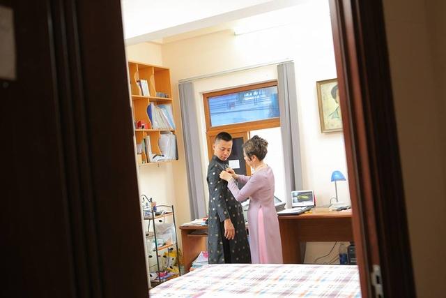 Chú rể được mẹ cài lại cúc áo trước khi lên đường sang nhà gái làm lễ ăn hỏi.