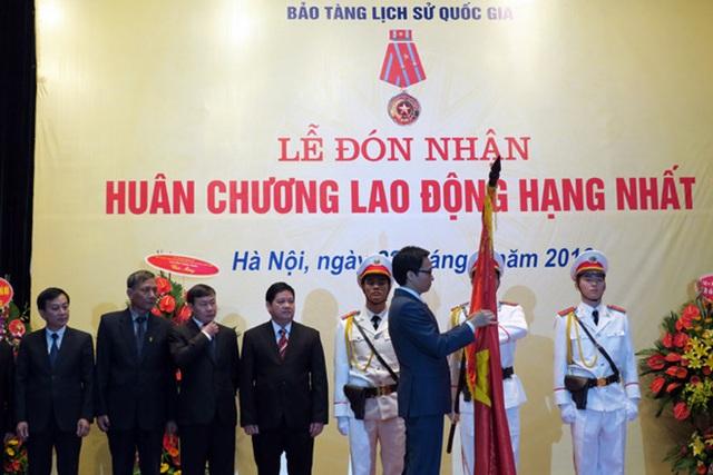 Phó Thủ tướng Chính phủ Vũ Đức Đam gắn Huân chương Lao động hạng Nhất lên lá cờ truyền thống của Bảo tàng Lịch sử Quốc gia. Ảnh: Hoàng Nguyên.
