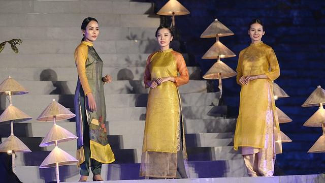 Dàn người mẫu khoe nét duyên dáng trong tà áo dài bên những chồng nón lá.