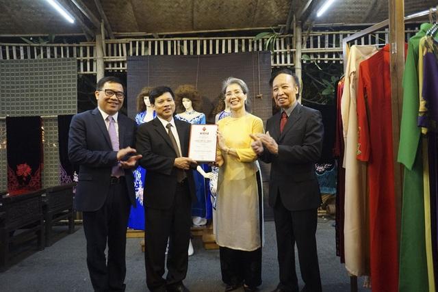 Đại diện BTC trao giấy chứng nhận cho nhà thiết kế La Hằng tại gian hàng của nhà thiết kế này.