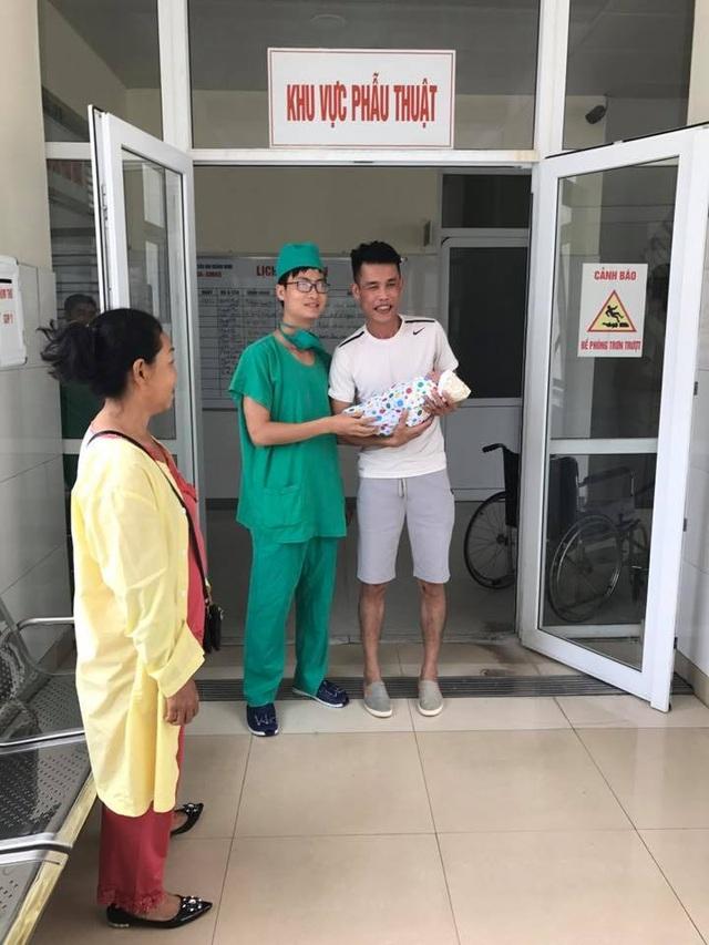 Hiệp Gà vui vẻ bế con trai chụp ảnh cùng bác sĩ hộ sinh khi con trai vừa chào đời tại bệnh viện. Ảnh: FBNV.