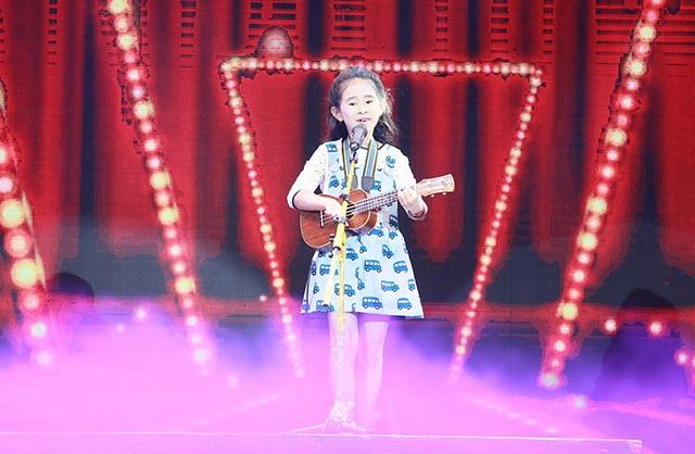 Một tài năng nhí tự tin biểu diễn với đạo cụ là cây đàn guitar bé xíu.