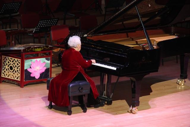 NSND Thái Thị Liên diện bộ áo dài nhung màu đỏ để biểu diễn piano khai mạc lễ kỷ niệm 60 năm ngày thành lập Học viện Âm nhạc.