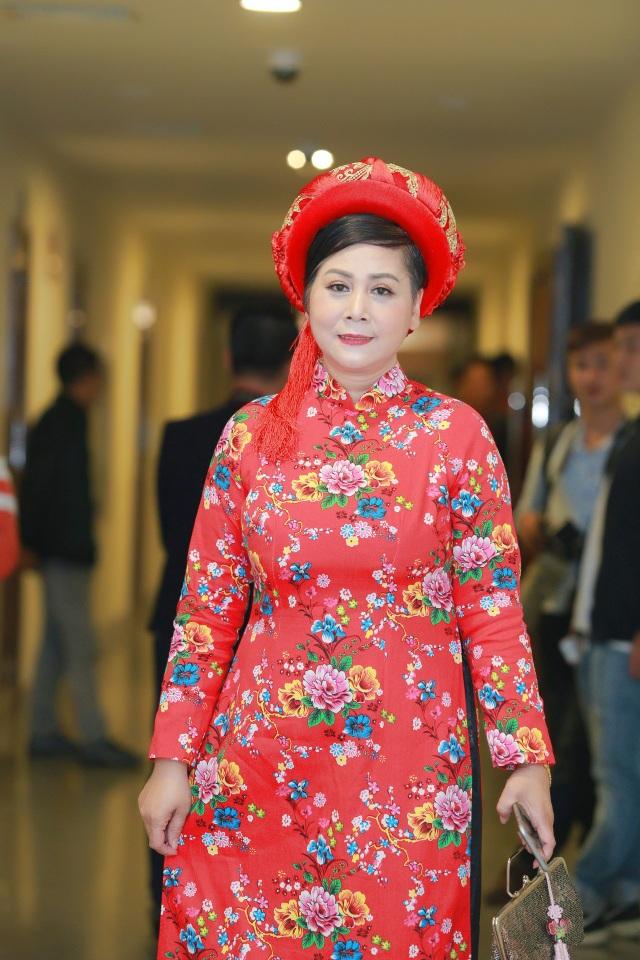 NSƯT Minh Hằng diện bộ áo dài hoa rất sặc sỡ.