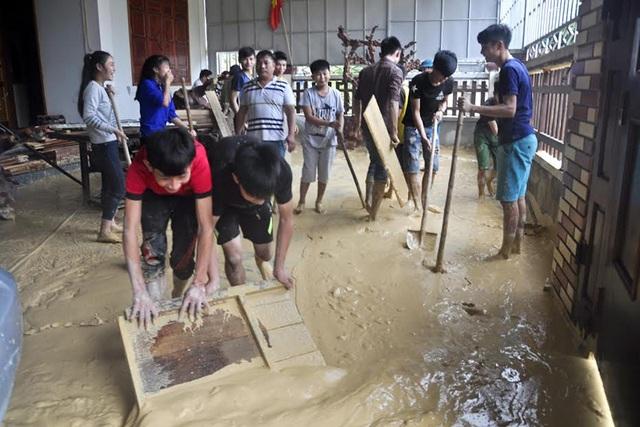 Đoàn viên thanh niên bốc dọn khối lượng bùn đất lớn tràn vào sân nhà ông Sỹ.