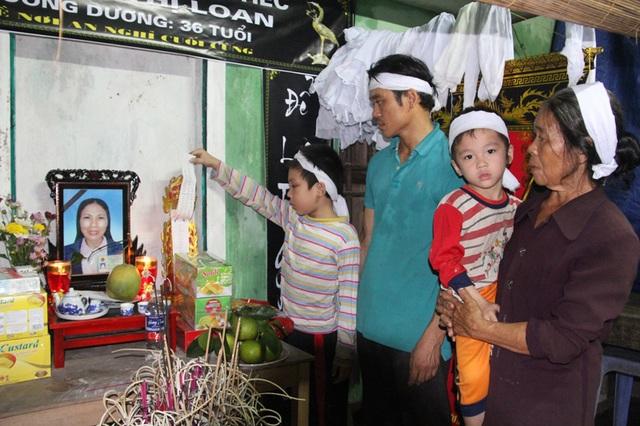 Hai bé Nguyễn Đình Quyết, 9 tuổi, học lớp 3 và bé Nguyễn Đình Huy, 4 tuổi- đầu chít khăn tang cùng bà nội và bố đứng bên bàn thờ của người mẹ thân thương.