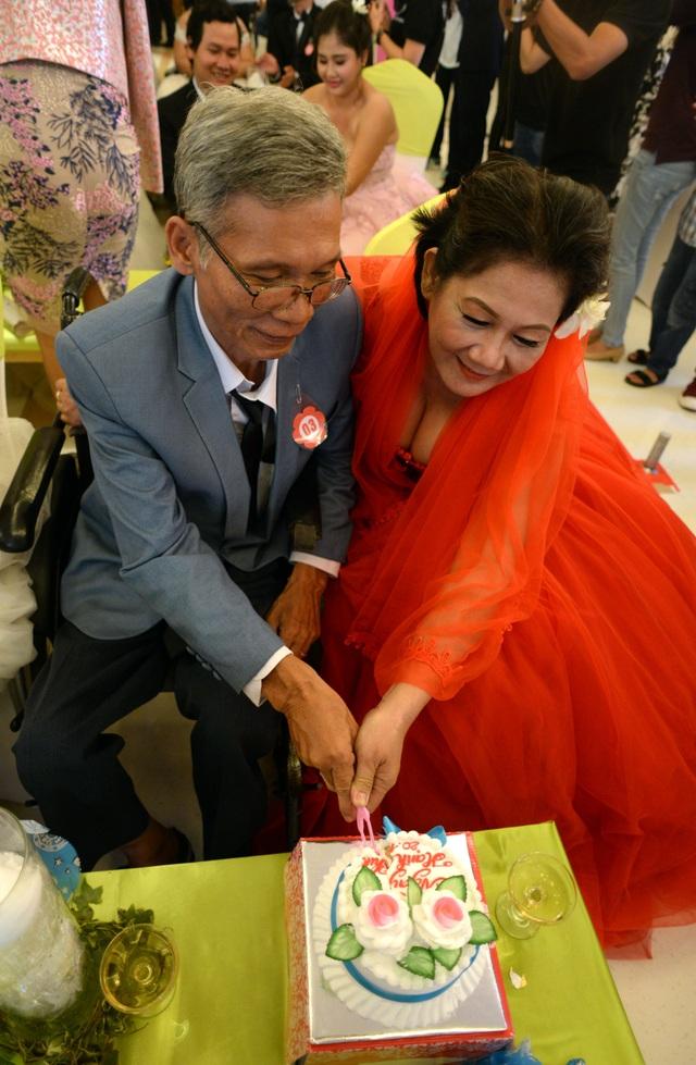 Cô dâu, chú rể tóc đều đã điểm bạc cùng nắm chặt tay nhau cắt chiếc bánh cưới.