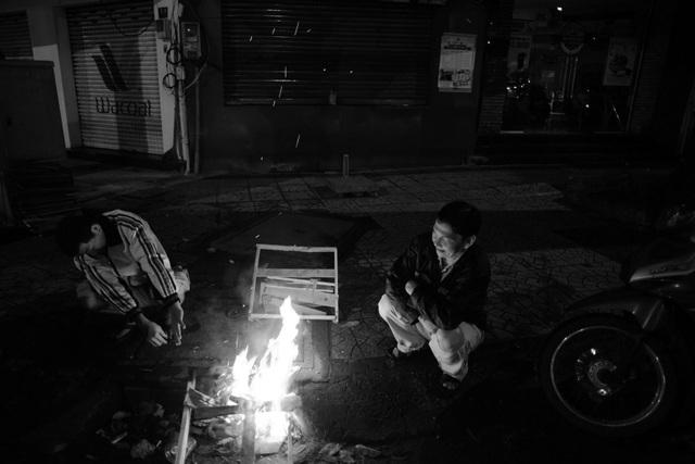 Hai ông Tới và Xỉn (55 tuổi) đã có 30 năm chạy xe ôm ở Sài Gòn. Chạy xe ban đêm ở vòng xoay Dân Chủ, 2 ông phải kiếm củi đốt để sưởi ấm trong lúc chờ khách.