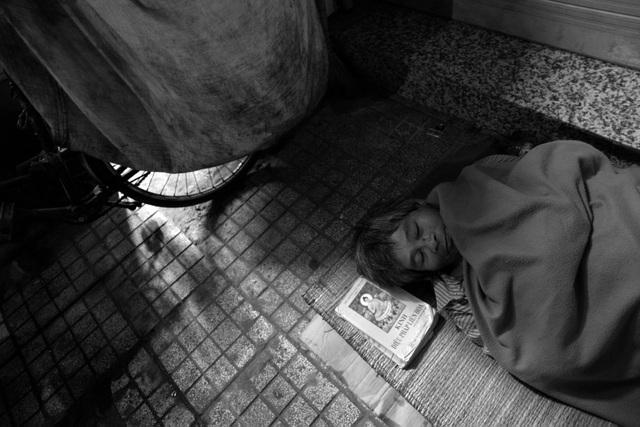 Ông Hòa (60 tuổi) trùm kín mền ngủ trong đêm lạnh cuối năm.
