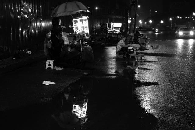 Nhiệt độ thấp, cùng những cơn mưa lất phất khiến trời càng lạnh hơn. Những người bán hàng rong phải mặc thêm áo mưa để chống rét.