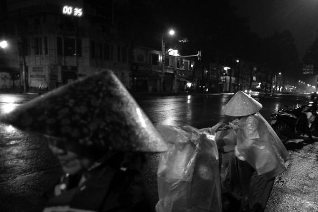 Khi đường phố vắng người, những phụ nữ hàng rong vẫn cố bám trụ lại chờ khách vãng lai ghé mua hàng.
