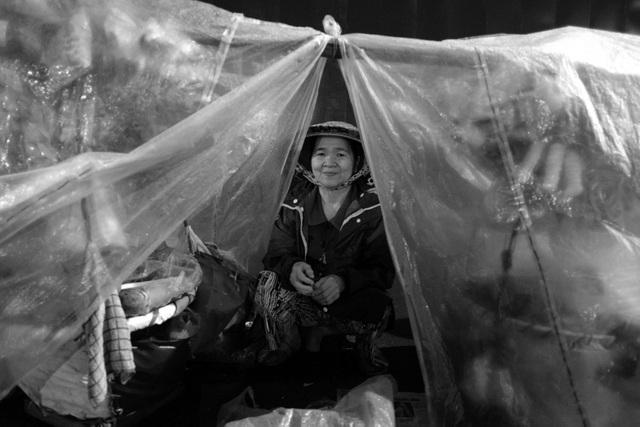 Bà Thanh nép mình bên trong gánh hàng rong được che chắn bởi nilon để tránh gió.