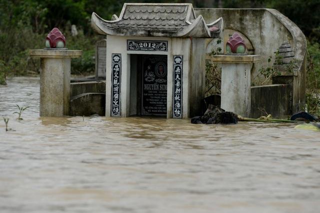 Không những nhà cửa của người dân bị ngập nước, các ngôi mộ ở khu vực này cũng chìm trong nước lũ nhiều ngày nay.