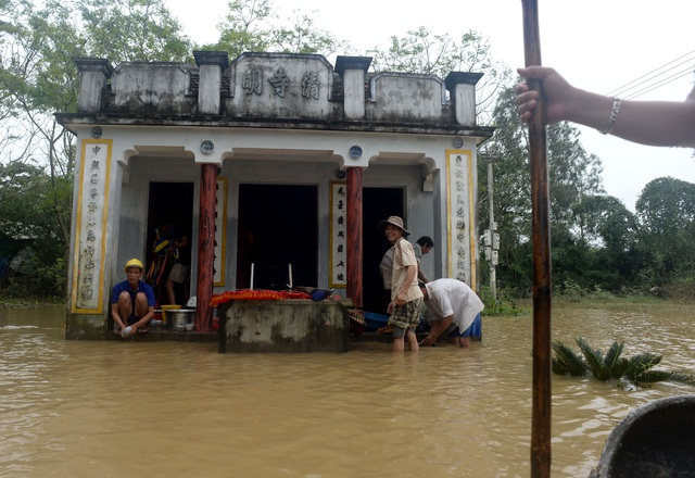 Người dân trong thôn Huỳnh Mai chung tay dọn dẹp lại đồ đạc trong ngôi miếu thờ trước thôn.