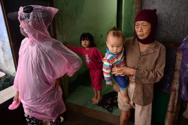 Bà Phan Thị Thạnh (71 tuổi, ngụ thôn Nhơn An, xã Phước Thuận, Tuy Phước) bị nước lũ cô lập nhiều ngày nay. Bà phải ở nhà giữ cháu để các con bơi ghe lên bờ mua tạm mì gói về ăn qua bữa.