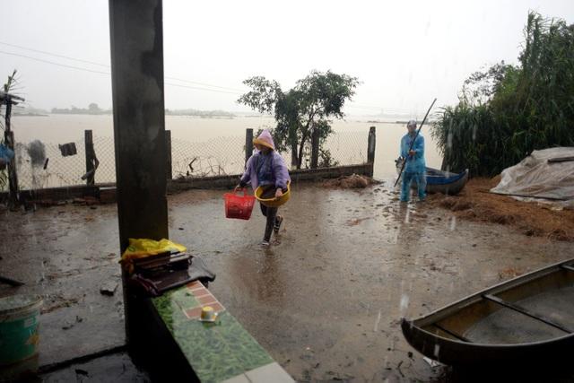 """Dù trời mưa lớn, anh Nguyễn Văn Hùng (32 tuổi) vẫn phải chống ghe đưa vợ lên bờ mua tạm ít đồ ăn vì nhà đã hết đồ dự trữ. """"Nhà đã hết mì gói từ ba ngày nay, đành phải chống ghe đi trong mưa lớn chở vợ đi mua ít đồ về ăn tạm. Vợ chồng tôi thì chịu đói được chứ các con còn nhỏ, lại có mẹ già nên đành phải đi""""."""